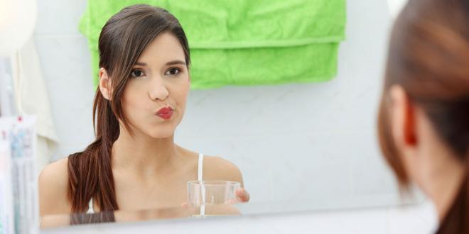 Oil Pulling girl in bathroom rinsing mouth